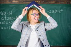 Effective method to remember information. Forget important information. Keep in memory. Improve memory skill. Woman. Teacher with book as roof on head royalty free stock photo