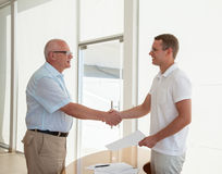 Effective negotiate. Two businessmen shake hands in office stock photography