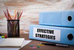 Effective Strategies, Office Binder on Wooden Desk. On the table. Colored pencils, pen, notebook paper Royalty Free Stock Images