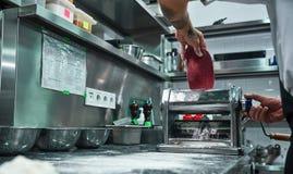 Effectuer des pâtes L'image cultivée du roulement masculin de chef malaxent par la machine de pâtes tout en travaillant dans la c images stock