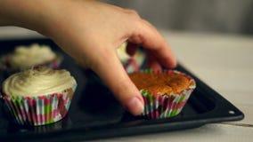 Effectuer des pains Cuisson des petits gâteaux La main emportent le gâteau du plateau de cuisson clips vidéos