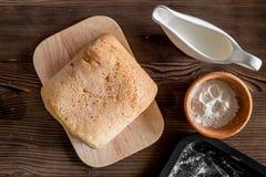 Effectuez le pain Pain et ingrédients sur la vue supérieure de fond en bois foncé de table photo stock