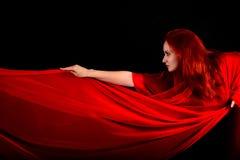 Effektiv härlig flicka med rött tyg och hår Arkivfoto