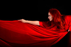 Effektives schönes Mädchen mit roten Gewebe und dem Haar Stockfoto