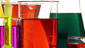 Effervescence in a beaker filled with red liquid. Several laboratory bottles of different shapes and colors stock footage
