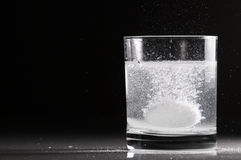 Effervescent pill in a glass of water Stock Photography