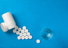Effervescent pills. Coming from a white tube shaping an arrow on blue surface Stock Images