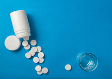 Effervescent pills top view. Effervescent pills coming from a white tube and a glass of water on a blue surface Stock Photo