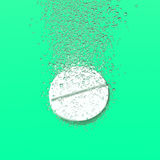 Effervescent tablet dissolbving. Effervescent medicine. Fizzy tablet dissolving. White round pill falling in water with bubbles. Green background. 3D Royalty Free Stock Photos