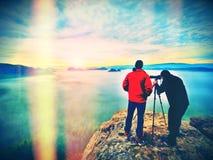Effet abstrait Silhouettes des photographes de l'homme Hommes sur la montagne Crête avec deux hommes prenant la photo Photos libres de droits
