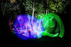 Effet au néon de peinture léger coloré de mouvement Utilisant une épée de clignotant d'enfants de lumière avec une longue exposit images libres de droits