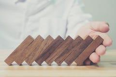 Effet de domino de bloc en bois de soutien de main d'homme d'affaires, risque commercial Images stock