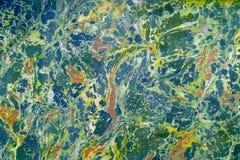 Effet de marbre abstrait sur l'eau, appelée l'ebru Couleurs jaunes, bleues et vertes mélangées Photos stock
