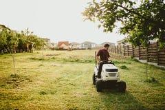 Effetto d'annata di abbellimento degli impianti Lavoratore maschio che guida un regolatore dell'erba del trattore Immagini Stock Libere da Diritti