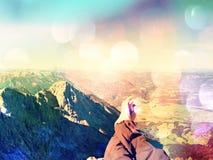 Effetto del grano del film Le gambe attraversate prendono un resto sulla traccia di montagna noiosa Gambe maschii sudate che si r Fotografia Stock Libera da Diritti