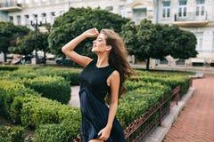 Efficiënt meisje met het lange krullende haar stellen op wind op groene yardachtergrond Zij heeft zwarte kleding en het dromen me royalty-vrije stock foto's