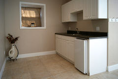 Efficiency apartment kitchen. View of an efficiency apartment kitchen with small fridge, sink and counters Stock Photo
