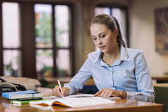Efficient student. Efficient female student at the library, she is sitting at desk and studying, education and self improvement concept Stock Image