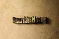 EFFICIENTEMENTE - il primo piano dell'annata grungy ha composto la parola sul contesto del metallo immagini stock libere da diritti