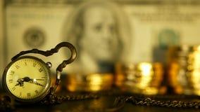 Efficienza della gestione Le pile aumentanti di monete dorate sul dollaro notano il fondo Retro orologio e fuoco molle archivi video
