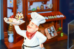 Effigy of a chief cook carrying. A tray of cakes in a restaurant in black forest Royalty Free Stock Images