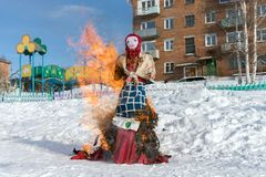 Effigy of the Shrovetide in Russian folk costume is burned in the snow during a traditional national holiday of Seeing off Russian. Winter. Effigy of the stock photography
