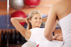 Effort. The girl does twisting on fitball with support of the trainer Royalty Free Stock Images