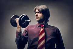 Effort. Young handsome man raises a weight Stock Photography