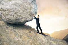 Effort concept. Side view of young businessman pushing huge rock up mountain. Beautiful background. Effort concept royalty free stock photos