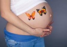 Effort de femme enceinte de Caucasien soucieux avec le papillon dans le studio d'estomac sur le fond gris Photos libres de droits