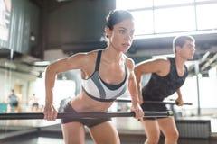 Effort. Female athlete exercising with fitness bar Stock Photo