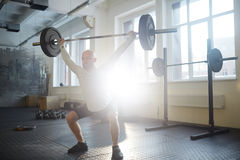 Effort. Sportsman squatting while lifting heavy barbell Stock Photography