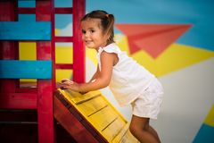 Effort is still worth it. Smiling little girl playing and climbing in playground. Space for copy stock photography
