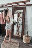 Effortless beauty.  Full length of attractive young woman taking. On the blouse and smiling while standing in front of the mirror at home Stock Photos
