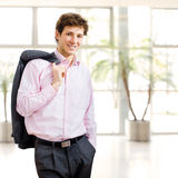 Effortless businessman in office building. Happy young businessman with jacket on shoulder and hand in pocket posing and smiling Stock Photography