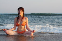 Effortless yoga. Posed girl sitting on sea coast Royalty Free Stock Photos