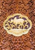 Effrayez le bois découpant des sculptures en mur dans le temple thaïlandais image stock