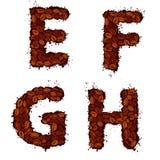 EFGH, Buchstaben des englischen Alphabetes, gemacht von den Kaffeebohnen, im Schmutz Stockfotos