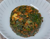 Efo riro with goat meat. Efo riro is a nutritious vegetable soup made from green leafy vegetables such as spinach and condiments. The condiments may include stock photo