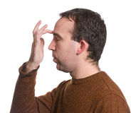 EFT Forehead. A man wearing a sweater is doing the emotional freedom technique by tapping on his forehead, isolated against a white background Stock Image