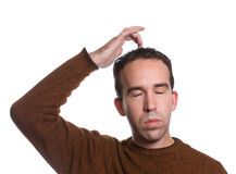 EFT Top of Head. A man wearing a sweater is doing the emotional freedom technique by tapping on the top of his head, isolated against a white background Royalty Free Stock Images
