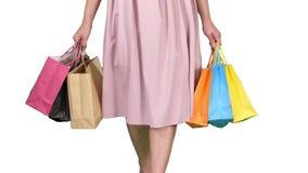 Efter dagen som shoppar bärande shoppa påsar för ung kvinna, medan gå på vit bakgrund stock video