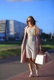 Efter dagshopping Närbild av bärande shoppingpåsar för ung kvinna, medan promenera gatan Arkivbild
