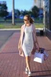 Efter dagshopping Närbild av bärande shoppingpåsar för ung kvinna, medan promenera gatan Royaltyfri Foto