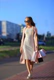 Efter dagshopping Närbild av bärande shoppingpåsar för ung kvinna, medan promenera gatan Arkivfoto