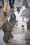 Efter regnet, skuggan i den lilla uttern på jordningen, benen av turisterna, royaltyfria foton