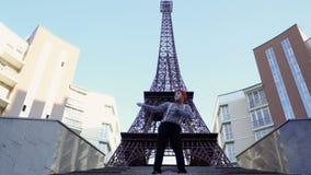 Efterapa i den röda basker avrivna skjortan som visar roliga platser på Eiffeltornbakgrund arkivfilmer