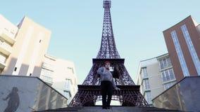 Efterapa i den röda basker som tillbaka flyttar sig på trappuppgång nära Eiffeltorn arkivfilmer