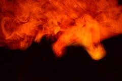 Efterföljd av ljusa exponeringar av den morotsfärgade flamman Bakgrund av abstrakt kulör rök royaltyfri fotografi