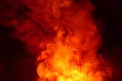 Efterföljd av ljusa exponeringar av den morotsfärgade flamman Bakgrund av abstrakt kulör rök royaltyfri foto